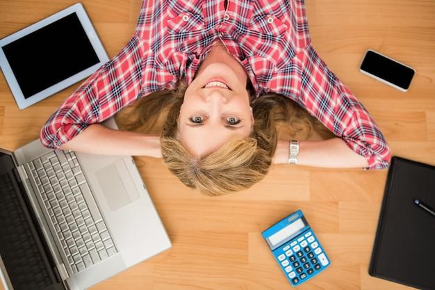 Femme souriante allongé sur le sol entouré d'articles de bureau