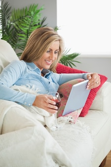 Femme souriante allongée sur un canapé, boire du vin et en utilisant un tablet pc
