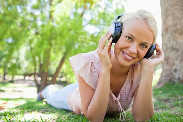 Femme souriante allongée sur l'herbe tout en écoutant de la musique