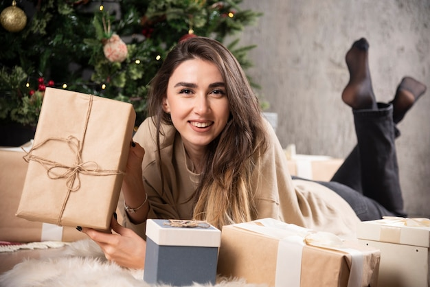 Femme souriante allongée sur un tapis moelleux et montrant un cadeau de noël.