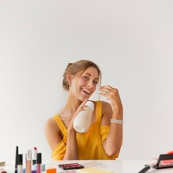 Femme souriante à angle élevé hydratant avec de l'eau
