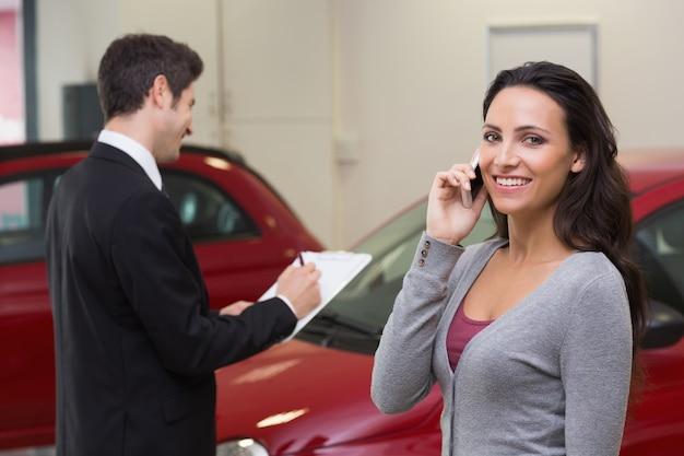 Femme souriante appelant quelqu'un avec son téléphone portable