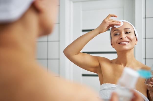 Femme souriante, appliquer de l'eau micellaire et nettoyer son visage. réflexion dans le miroir