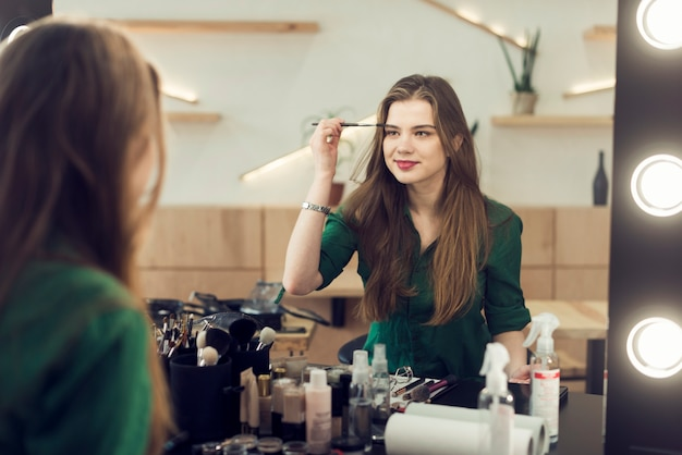 Femme souriante, appliquer le maquillage sur les sourcils