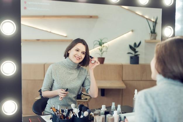 Femme souriante, appliquer le mascara