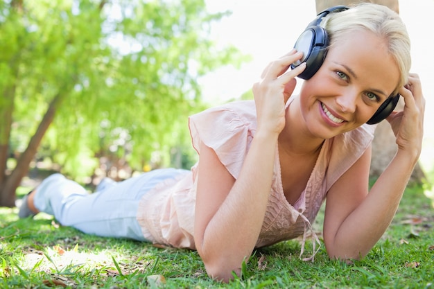 Femme souriante appréciant la musique sur l'herbe