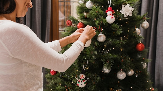 Femme souriante arrangeant une boule blanche sur le sapin
