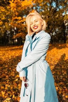 Une femme souriante assez élégante avec du rouge à lèvres rouge dans un manteau bleu à la mode se promène dans le parc avec un feuillage jaune en vacances ensoleillées d'automne