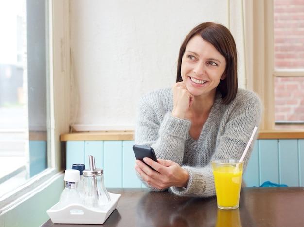Femme souriante, assis avec un téléphone mobile