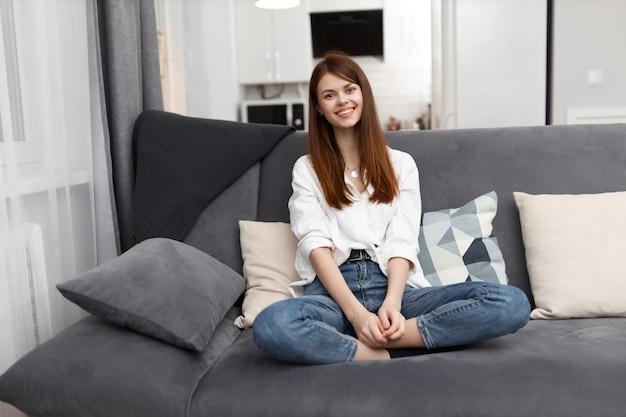 Femme souriante assise sur un canapé confortable dans un week-end en appartement