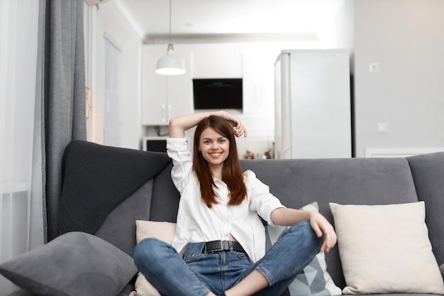 Femme souriante assise sur le canapé avec oreillers temps libre appartement confortable.