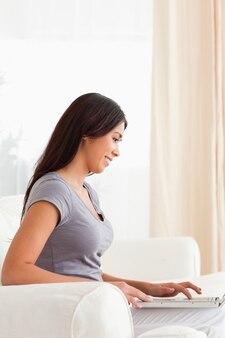 Femme souriante assise sur un canapé, travaillant avec un ordinateur portable