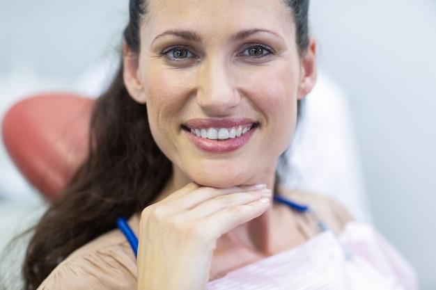 Femme souriante assise sur une chaise de dentiste