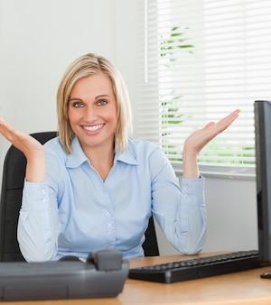 Femme souriante assise derrière un bureau sans avoir la moindre idée de ce qu'il faut faire ensuite