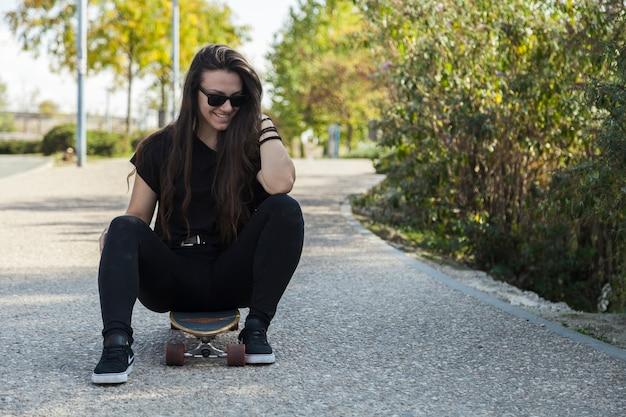 Femme souriante assise sur longboard