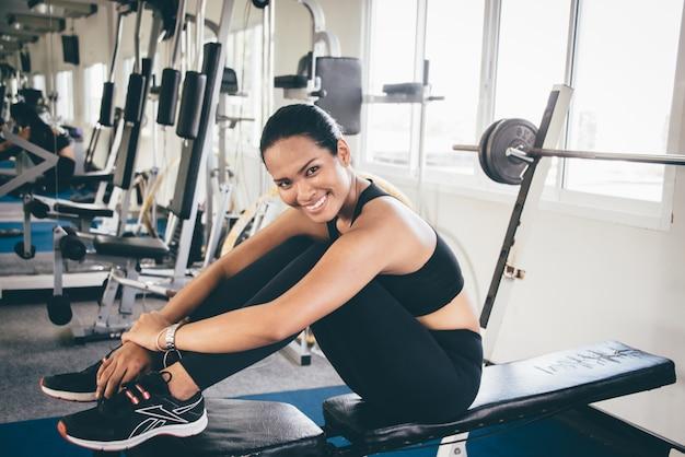 Femme souriante assise sur une machine de poids