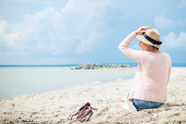 Femme souriante et assise sur la plage contre la mer