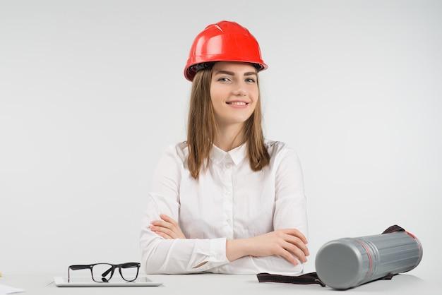 Femme souriante assise à la table en casque orange croisant les bras