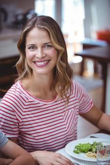 Femme souriante assise à la table à manger