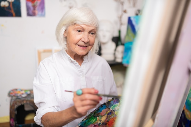 Femme souriante. attrayant femme âgée souriant tout en tenant le pinceau et la peinture sur toile