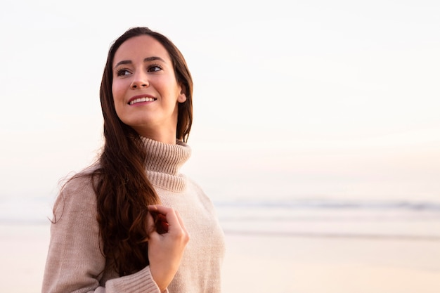 Femme souriante au bord de la plage posant avec espace copie