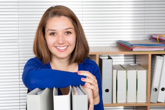 Femme souriante au bureau avec une pile de dossiers
