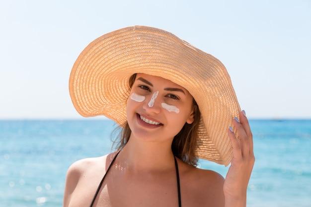 Une femme souriante au chapeau applique un écran solaire sur son visage. à l'indienne.