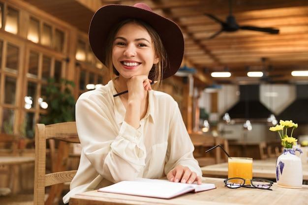 Femme souriante au chapeau assis à la table de café à l'intérieur