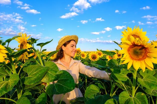 Femme souriante au chapeau de paille dans le champ de tournesol en fleurs au lever du soleil