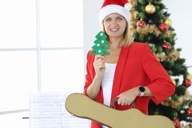 Femme souriante au chapeau de père noël tient la guitare sur fond d'arbre de noël