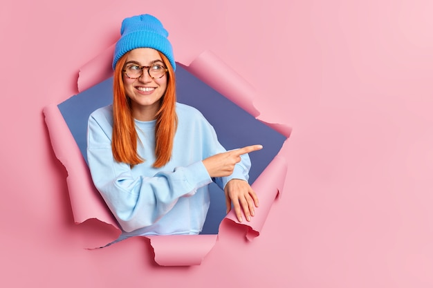 Une femme souriante au gingembre se sent optimiste en pointant sur l'espace de copie, porte des lunettes de chapeau bleu et un cavalier brise le papier
