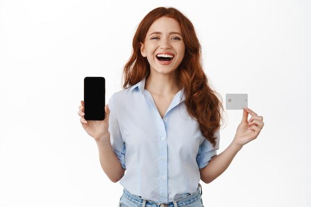 Femme souriante au gingembre tenant un smartphone et une carte de crédit sur blanc
