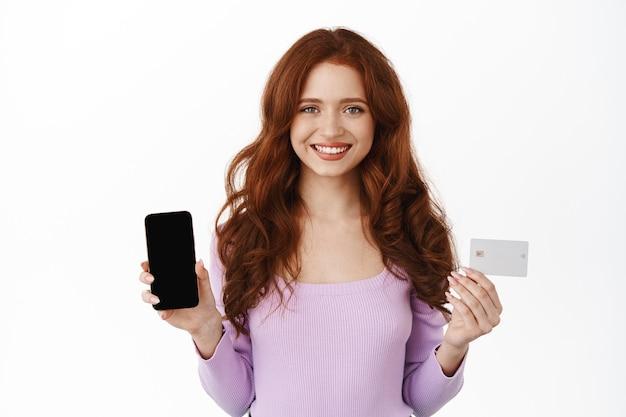 Femme souriante au gingembre tenant un smartphone et une carte de crédit