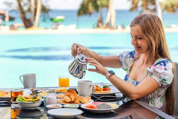 Femme souriante au petit-déjeuner américain buvant du jus d'orange à côté de la piscine