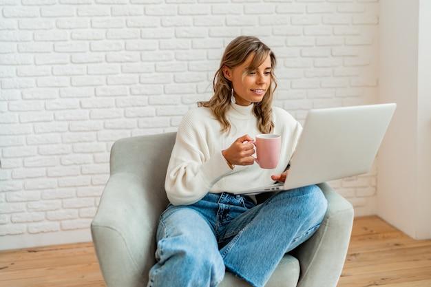 Femme souriante aux cheveux blonds ondulés assise sur un canapé à la maison travaillant sur un ordinateur portable et tenant une tasse de café