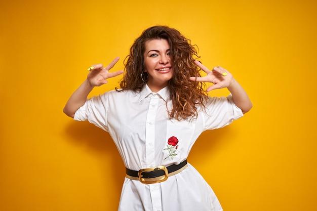 Une femme souriante aux cheveux bouclés dans une chemise blanche lève les mains au niveau des yeux. tient ses doigts avec la lettre v au niveau des yeux.
