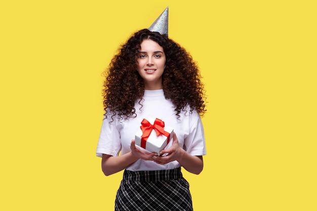 Femme souriante aux cheveux bouclés wering cap holding boîte-cadeau d'anniversaire sur fond isolé jaune