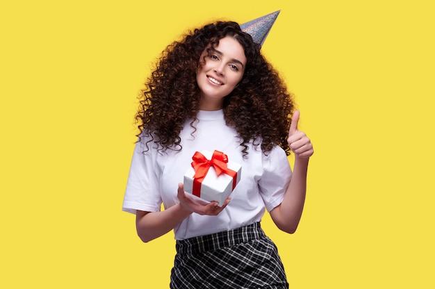 Femme souriante aux cheveux bouclés wering cap holding boîte-cadeau d'anniversaire et montrant le geste du pouce vers le haut sur fond isolé jaune