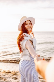 Une femme souriante aux cheveux longs au chapeau tient la main de son petit ami le long du sable de la plage de l'océan vide au coucher du soleil. suivez-moi concept.