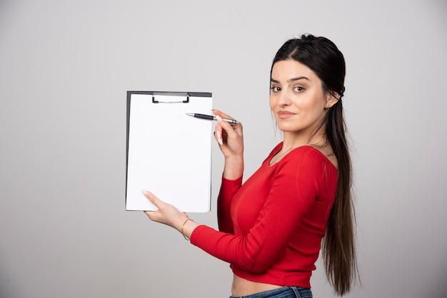 Femme souriante aux cheveux longs montrant un presse-papiers avec un crayon.