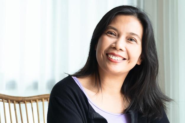 Femme souriante aux cheveux longs noirs assis à l'intérieur