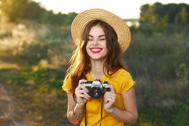 Femme souriante aux yeux fermés et avec un appareil photo dans ses mains dans un chapeau sur la nature. photo de haute qualité