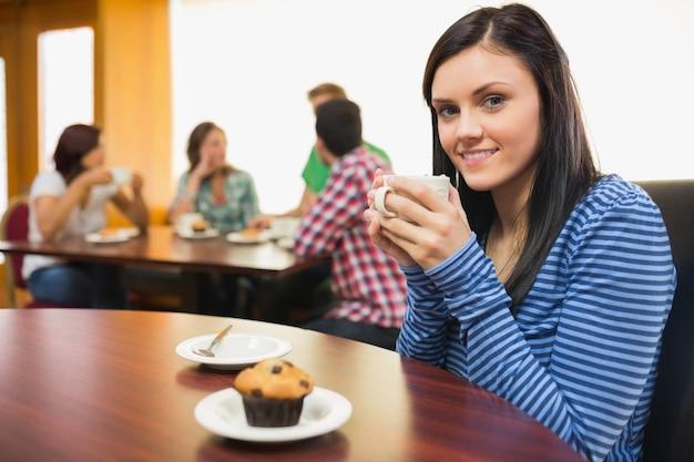 Femme souriante ayant un café et un muffin au café