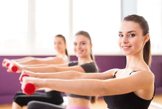 Femme souriante avec des ballons d'exercice et des haltères dans la salle de gym.