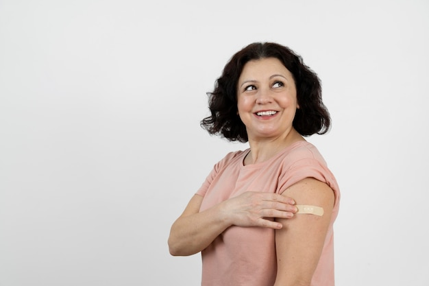 Femme souriante avec un bandage sur le bras après le vaccin