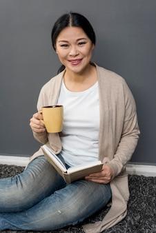 Femme souriante, boire du café et lire