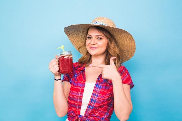 Femme souriante boire du jus rouge. portrait en studio avec fond bleu et espace de copie.