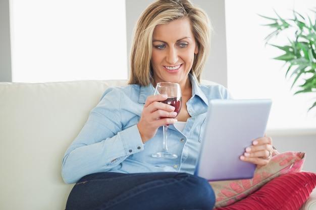 Femme souriante, boire du vin et en utilisant un tablet pc