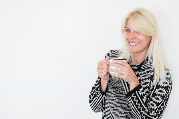 Femme souriante avec une boisson chaude en détournant les yeux