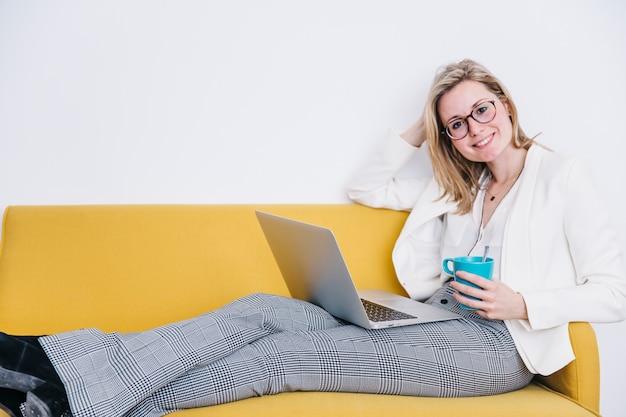 Femme souriante avec boisson chaude et un ordinateur portable